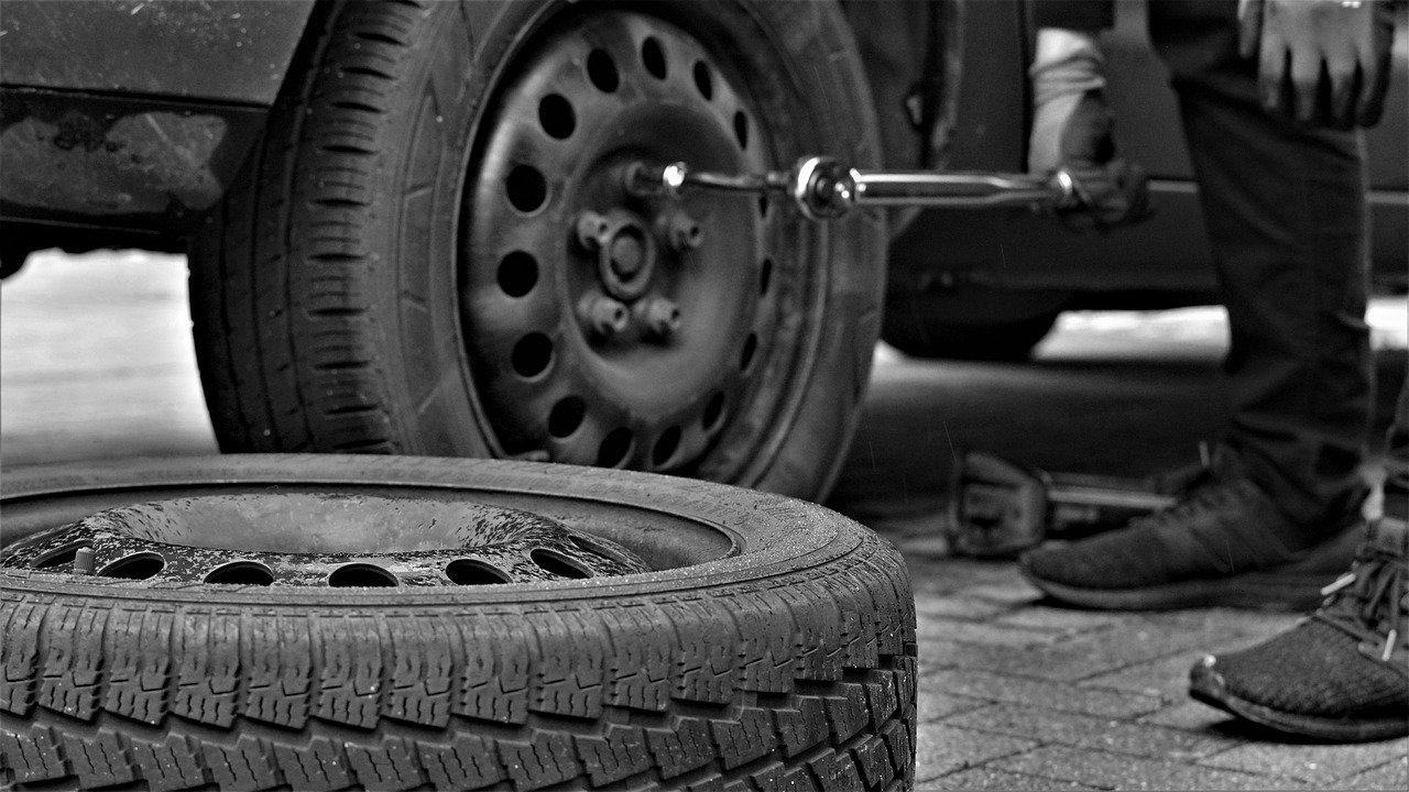 Homme changeant pneus d'une voiture