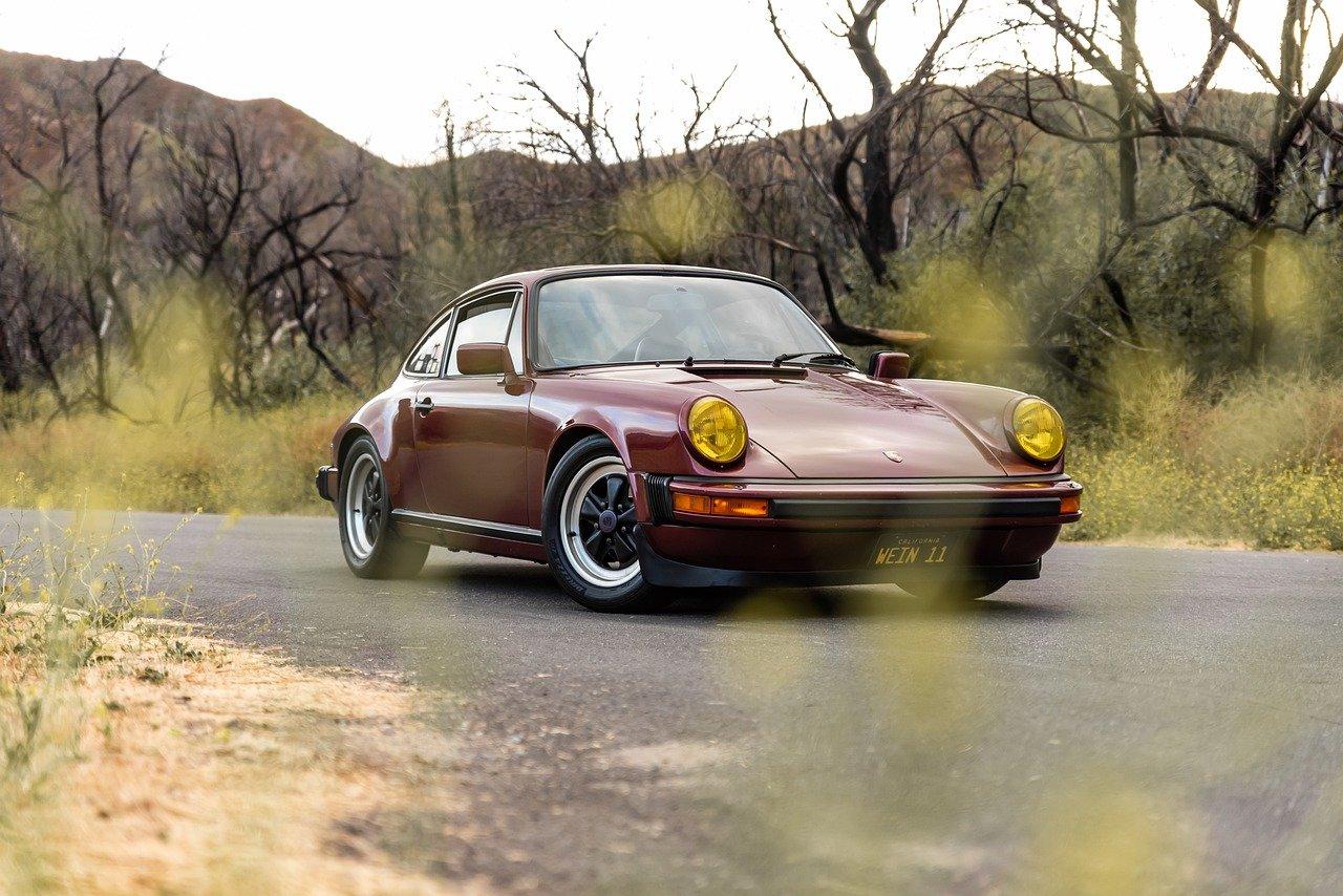 Porsche bordeaux sur route de campagne
