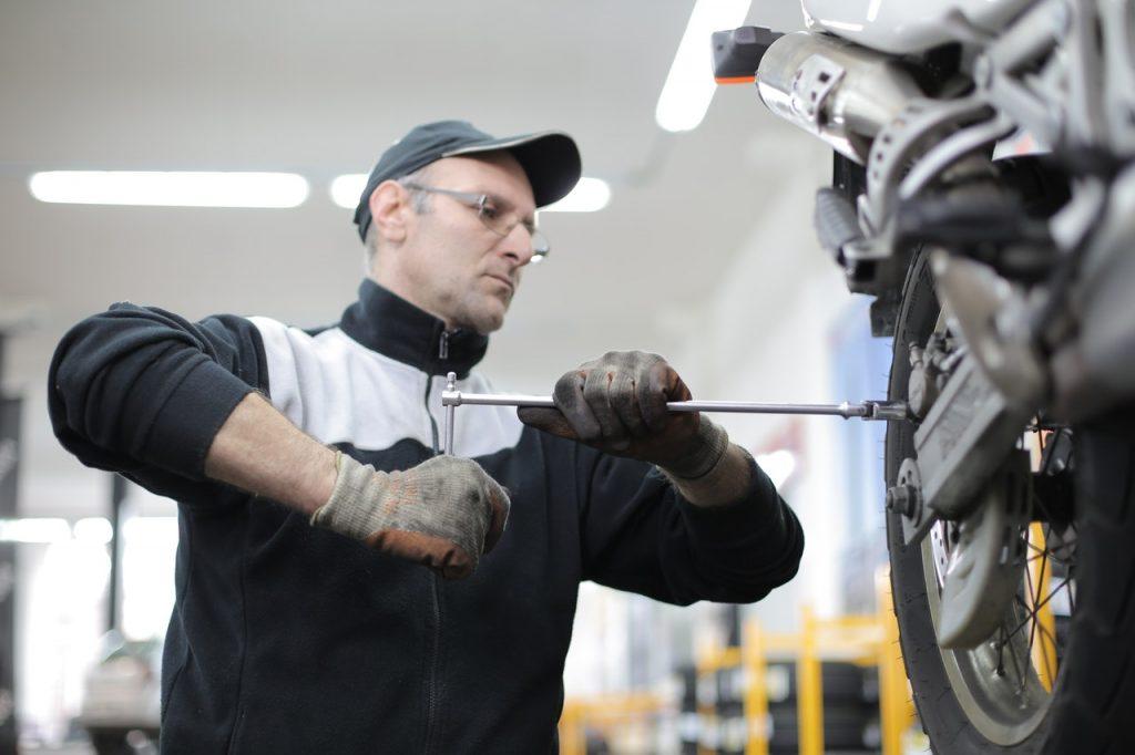 Garagiste changeant la roue d'une moto