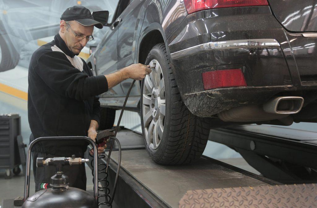 Garagiste contrôlant la pression des pneus
