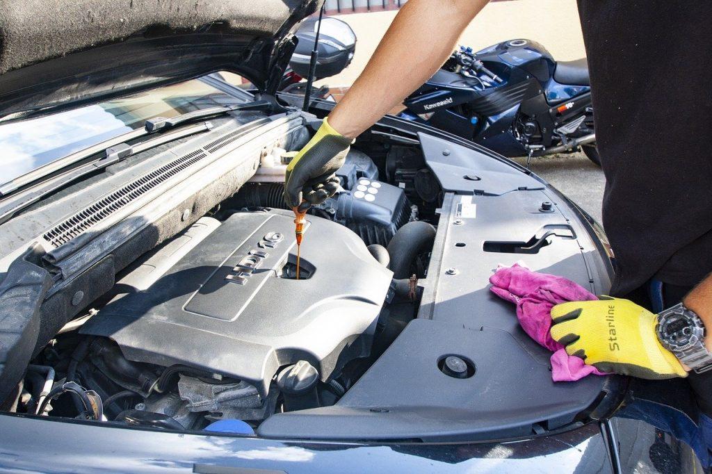 Garagiste vérifiant le niveau d'huile d'une voiture
