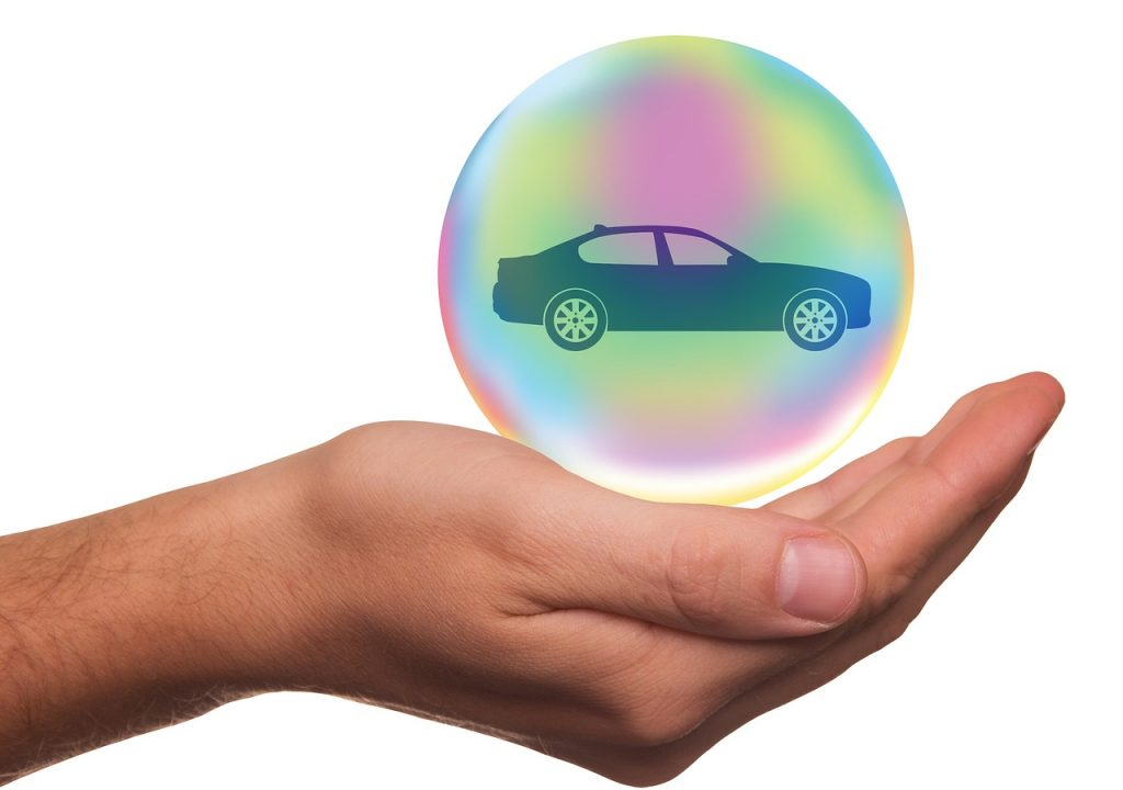 Main tenant bulle contenant une voiture, protection, assurance